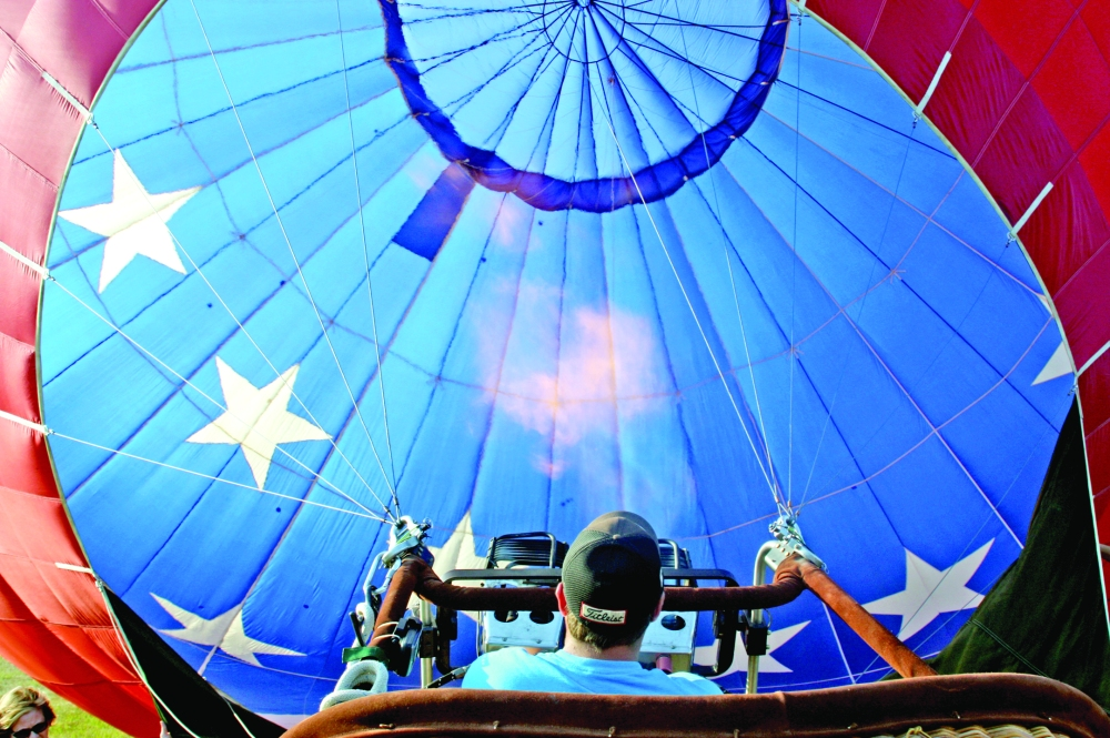"Hot-air balloon pilot Spencer Conlin readies ""Old Glory"" to launch from a field near Macomb's YMCA on Thursday, Sept. 5, 2013, in advance of the annual balloon rally in Macomb, Ill. When asked how he'd control its direction to land at WIU's Vince Grady Field, he said often ""it's at the mercy of the wind."""