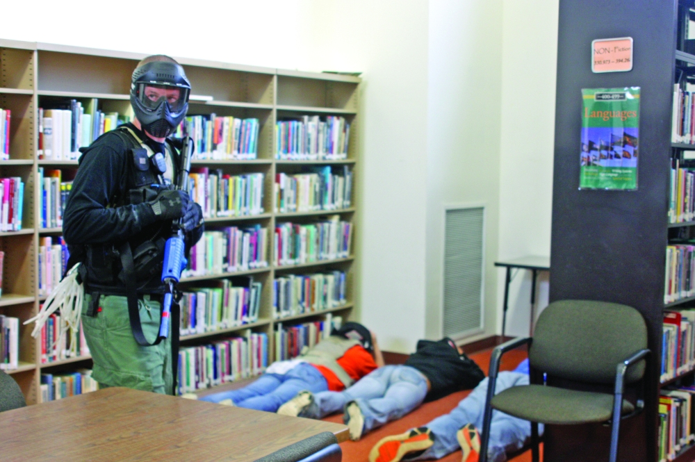 One of several training officers looks over the library at Macomb High School after victims, roleplayed by students, were ushered to a corner of the room during an active shooter simulation on Wednesday, June 11, 2014. The scenarios carried out were based on real school shootings. This one entailed a shooter who'd taken people hostage.