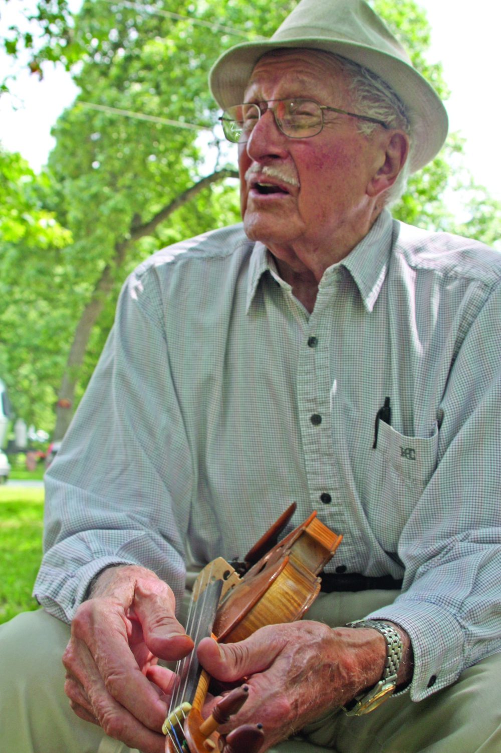 "Walter Jones, 90, of Hamilton holds out a fiddle he made during the Spring Lake Bluegrass Festival and Jam on Saturday, July 19, 2014, in Macomb, Ill. Jones jammed with a small group of other senior-aged musicians away from the festival's main performances and secluded under a tree canopy; however, he was the only one two bring an instrument he'd crafted himself over an expansive, decades-long career. ""I've repaired violins,"" he said. ""I've even repaired one in Switzerland."""