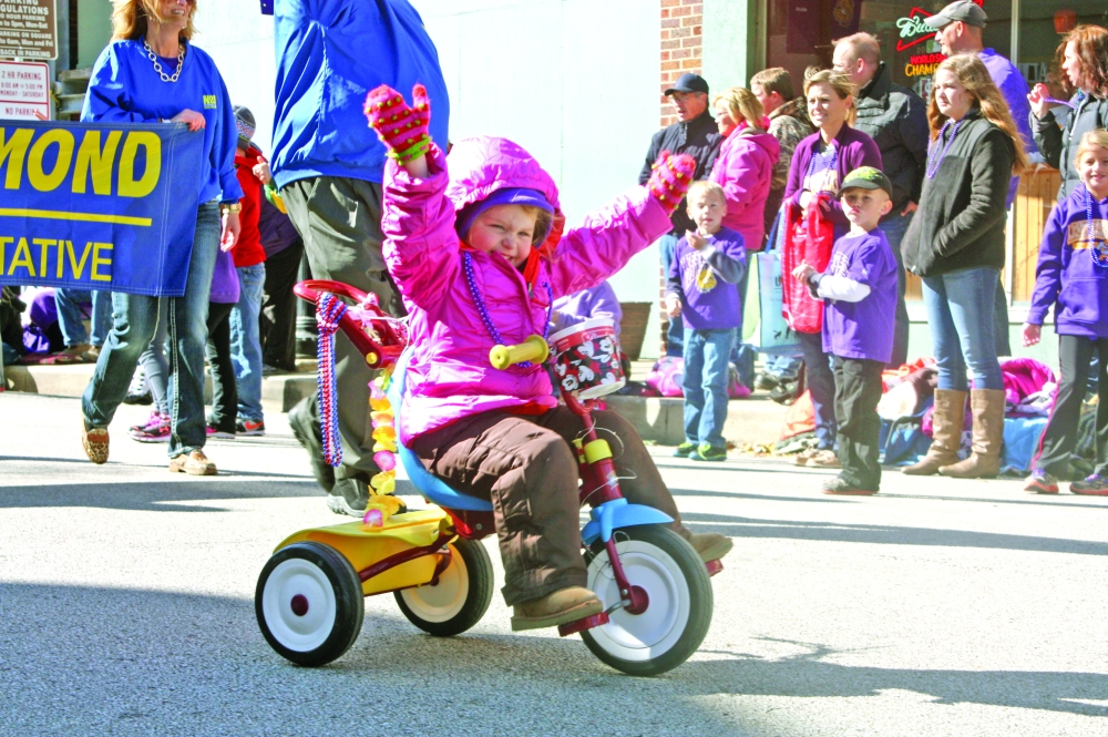 A young girl rides her tricycle with no hands with marchers from the office of state Rep. Norine Hammond, R-Macomb, during the Saturday, Oct. 4, 2014, Western Illinois University Homecoming parade as it made its way east down Carroll Street in downtown Macomb, Ill. This parade is one of the two biggest each year.