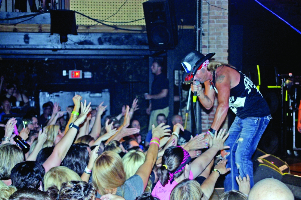 Rocker Bret Michaels touches hands with fans as they reach up during his performance Thursday, June 27, 2013, at the Forum in Macomb. The crowd pushed toward the stage throughout his concert, which fell on the first day of Heritage Days 2013 weekend.