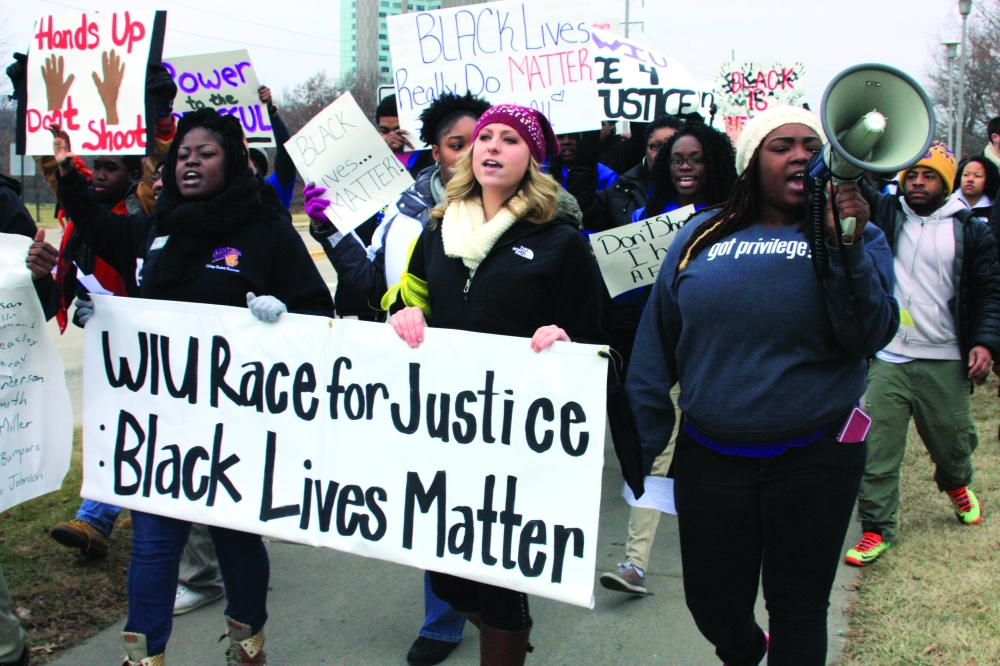 "Hundreds of Western Illinois University students, faculty and community members marched through the Macomb campus on Friday, Dec. 12, 2014. What was dubbed a solidarity march and rally entitled, ""WIU Race 4 Justice: Black Lives Matter,"" came in the wake of the highly publicized deaths of young unarmed black men, Michael Brown and Eric Garner, who in separate altercations with police in different states were killed earlier in the year."