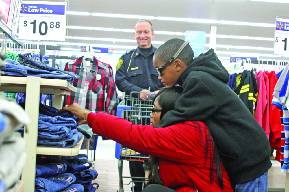Delorean Buckner, 7, hugs his mother, Felicia Jones, as she looks through pairs of jeans at Walmart Tuesday, Dec. 9, 2014, and Macomb Police Chief Curt Barker watches on. The Lincoln School student was one of about more than 60 total children to benefit from that year's Macomb Shop with a Cop program.
